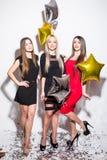 Jolies jeunes femmes avec les ballons en forme d'étoile et la danse de confettis et la partie de avoir Image stock