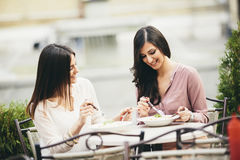 Jolies jeunes femmes prenant le déjeuner dans le restaurant Photographie stock libre de droits