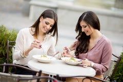 Jolies jeunes femmes prenant le déjeuner dans le restaurant Image stock