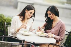 Jolies jeunes femmes prenant le déjeuner dans le restaurant extérieur Photographie stock libre de droits