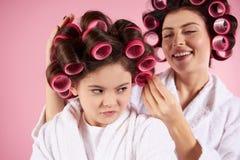 Jolies mère et fille dans des bigoudis de cheveux Image libre de droits