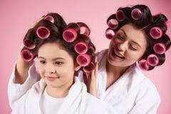 Jolies mère et fille dans des bigoudis de cheveux Images stock
