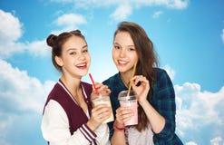 Jolies secousses heureuses de lait boisson d'adolescentes Photos stock