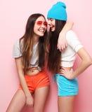 Jolis adolescentes ou amis de sourire heureux étreignant au-dessus du rose Photographie stock libre de droits