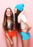 Jolis adolescentes ou amis de sourire heureux étreignant au-dessus du rose Photographie stock