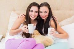 Jolis amis ayant le café sur le lit Photo stock