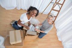 Jolis amis déballant des boîtes dans la nouvelle maison Images stock