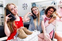 Jolis amis intimes faisant l'achat ensemble tenant de nouvelles chaussures comme téléphones dans le magasin de mode Images stock