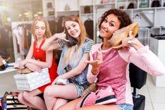 Jolis amis intimes faisant l'achat ensemble tenant de nouvelles chaussures comme téléphones dans le magasin de mode Image libre de droits