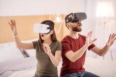 Jolis couples étonnés voyant le monde virtuel Images stock