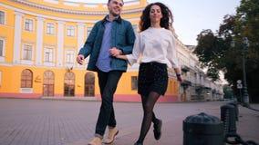Jolis couples de l'homme et de la femme courant tenant des mains dans la ville d'automne Paires heureuses élégantes ou étudiants  banque de vidéos