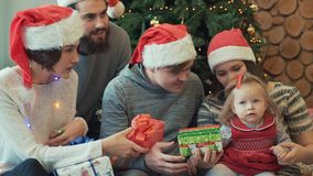Jolis couples gais de famille et leurs amis s'asseyant avec le bébé donnant ses différents présents et montrant des lumières banque de vidéos