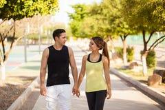 Jolis couples marchant au parc Photos stock