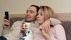 Jolis couples observant un film à la maison, le thé potable de femme et parlant à un associé Photo stock