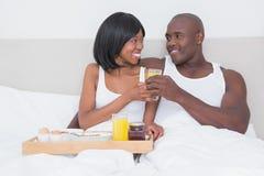 Jolis couples prenant le petit déjeuner dans le lit ensemble Images stock