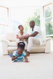 Jolis couples se reposant sur le divan et leur fille à l'aide du comprimé numérique images libres de droits