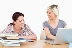 Jolis femmes apprenant avec l'ordinateur portatif et les livres Photographie stock libre de droits
