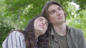 Jolis jeunes couples de portrait dans des vêtements sport se reposant au banc parlant et tenant des mains fille de gar?on heureus clips vidéos
