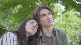 Jolis jeunes couples de portrait dans l'amour portant les vêtements sport se reposant au banc parlant et tenant des mains Fille h clips vidéos