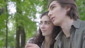 Jolis jeunes couples de portrait dans l'amour portant les v?tements sport se reposant au banc parlant et tenant des mains Fille h clips vidéos