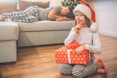 Jolis petits poses et regards de fille sur la caméra Elle tient la boîte rouge avec le présent dans des mains La fille tient le d images libres de droits