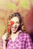 Jolis rires enthousiastes de fille avec le coeur rouge sur le bâton photographie stock libre de droits