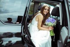 Jolis sourires de jeune mariée se reposant dans la voiture Images libres de droits