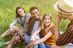 Jolis types et filles se reposant en parc Photos stock