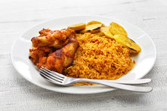 Jollof rice, west african cuisine. Jollof rice with chicken and fried plantain, west african cuisine Royalty Free Stock Photos