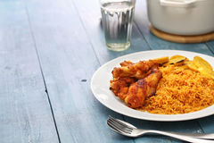 Jollof rice, west african cuisine. Jollof rice with chicken and fried plantain, west african cuisine Royalty Free Stock Images