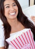 Jolly asian woman eating pop corn Stock Photography