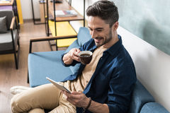 Jolly bearded guy having rest using computer gadget indoor Royalty Free Stock Photos