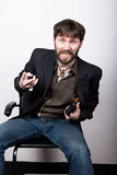 Jolly bearded man in a jacket and jeans, sitting on a chair and holding a gun. gangster concept Stock Photo