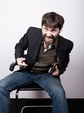 Jolly bearded man in a jacket and jeans, sitting on a chair and holding a gun. gangster concept. Negotiations went not Royalty Free Stock Image