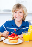 Jolly boy eating waffles with strawberries. In the kitchen Stock Photo