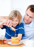 Jolly boy and his father putting honey on waffles Royalty Free Stock Photography