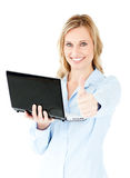 Jolly businesswoman holding a laptop with thumb up Royalty Free Stock Photography