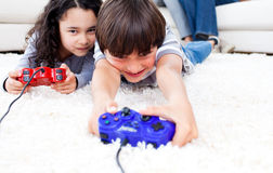 Jolly children playing video games. Lying on the floor with their parents in the background Stock Image