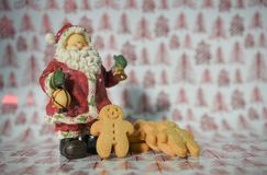 Jolly Christmas food photography gingerbread man with Santa Claus decoration ornament on red tree wrapping paper background Royalty Free Stock Images