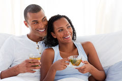 Jolly couple drinking a cup of tea on their bed Stock Photography