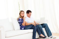 Jolly couple using a laptop sitting on sofa Royalty Free Stock Photo