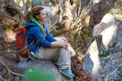 Jolly cute Girl sitting on fallen Tree in Spring Forest Stock Photography