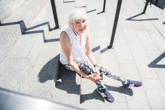Jolly elderly woman relaxing while exercising on stairs outdoor Royalty Free Stock Photos