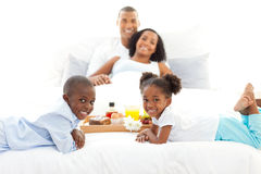 Jolly family having breakfast in the bedroom Stock Photo