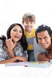 Jolly family reading book together Stock Photos