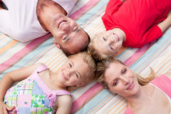 Jolly family sleeping lying on the grass. In a park Stock Photo