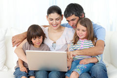 Jolly family using a laptop on the sofa. At home Stock Photos