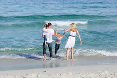 Jolly family walking on the sand Stock Photography