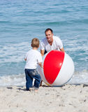Jolly father and his son playing with a ball. At the beach Royalty Free Stock Images