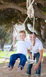 Jolly father pushing his son on a swing. In a park Stock Photography